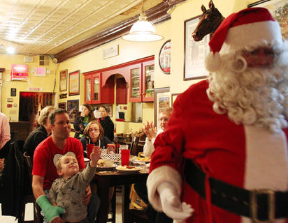 Don't go, Santa! Hamish Garvey, 4, reaches out for Santa Claus as he says his goodbyes at Mammy's Kitchen in downtown Bardstown during Light Up Bardstown last Friday night. Dad Steve Garvey stands by for 