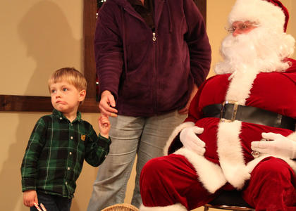 ABOVE — Robert Allwright, 3-and-a-half, isn't so sure about that Santa guy. Allwright and his mother, Emily Allwright, visited Light Up Bloomfield Nov. 26, 2011, at the Bloomfield Civic Center. Robert did enjoy dancing to the live Christmas tunes of Mike Douglas, Bardstown, and Will Brooks, Bloomfield.