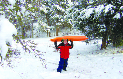 """After a sled ride down, Lincoln Boone hikes back up the hill. He and his siblings """"have had great fun in the snow over the past few weeks,""""  mom, Camille Boone, said. The pictures were taken on the Boone property on Marks Lane. Submit your """"Fun in the Snow"""" pictures online."""