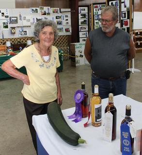 Sarah June Jewell of Bloomfield admires a zucchini at the Nelson County Fair. At right is her son, Gary Jewell.