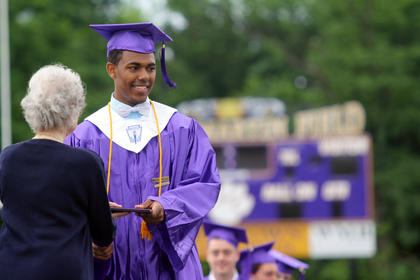 Marcus Cosby smiles for the camera after he receives his diploma from Bardstown City Schools board member Margie Bradford at Bardstown High School's graduation Saturday.