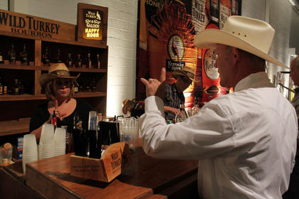Dooley Mattingly, New Haven, orders a drink at the Wild Turkey Sit 'n' Sip Saloon at Thursday night's Boots & Bourbon event, complete with live country music, cornhole and bull riding.