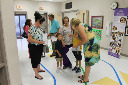 Principal Michelle Ryan, right, and Jane Leake greet Dalten Mattingly, center, his brother, Kaleb Mudd, and mother, Samantha Mudd at Bardstown Primary School on the first day of classes.