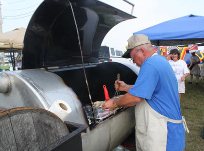 """Mark Sims, Culvertown, inspects the barbecue on the grill belonging to his team, the Pit Crew Outlaws, consisting of members from Culvertown and Holy Cross. This was Sims' first cook-off. """"Some of it's been fun but this crunch time now, getting to presentation — it's been pressure-packed,"""" he said. """"You take up your best piece of meat (to the judges). We did 60 chicken wings. We're picking six to send."""" Sims' fellow team members were Mike Burba, Kenny Mattingly and Alan Sims."""