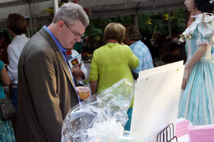 """Rob Smotherman, of Bardstown, browses some items on display during a silent auction at Doo Dah Day Saturday in front of the J. Dan Talbott Amphitheatre. The event marked the opening of """"The Stephen Foster Story,"""" which is in its 55th year."""