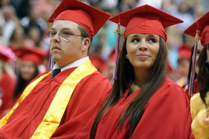 A Nelson County High School graduating senior looks into the crowd to try to find her family during graduation.