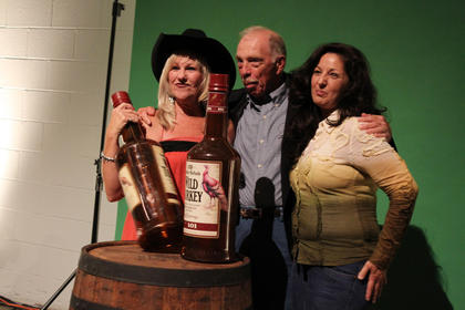 Melinda Mooneyhan, left, Ron Provine and Toni Hutchins, all of Bardstown, pose for a picture at Boots & Bourbon Thursday night, where guests could dance to live country music, play cornhole or ride a mechanical bull.