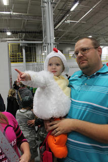 Aubrie Mattingly, dressed as a little chicken, points to something while her father, Chad Mattingly, carried her while the family trick-or-treats at the Guthrie Opportunity Center.
