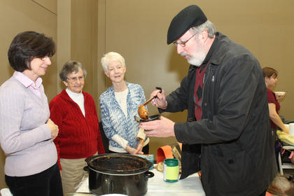 "Father Bill Hammer, pastor of St. Joseph Parish, helps himself to some of the Sisters of Charity of Nazareth Chili at the Souper Bowl of Caring Saturday night at the church hall. The sisters' recipe, which is served at the convent, was the winner of this year's chili competition, besting those of the Knights of Columbus and Greg Blevins. From left are St. Vincent de Paul volunteer Mary Manion, Sr. Earline Hobbs and Sr. Ann Boone. Theresa Hurst and her granddaughter Kaylie won  the soup competition with their ""Nana's Potato Soup."" The soup and chili dinner was a benefit for the St. Vincent food pantry in Bardstown."
