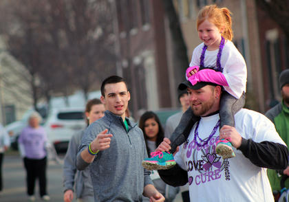 Clinging tightly to Dad, 5-year-old Kinslee Carter enjoys her family's participation in the third annual Forget Me Not Fun Run Saturday. Carter's great-grandmother suffers from Alzheimer's, which the Fun Run is for.