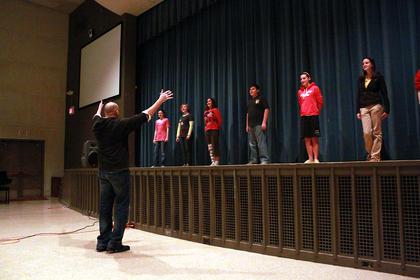 """Warren encourages a group of students to belt out the words to """"Ding Dong, the Witch is Dead."""" As part of the auditions, the young actors were required to sing a part of the song twice."""