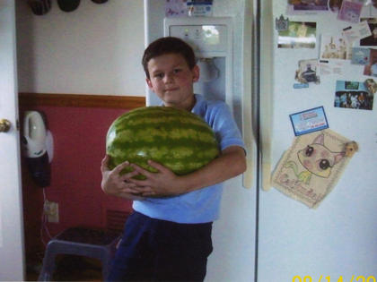 Jacob Avis is holding the 10-pound watermelon that he and his brother, Matt, grew at their grandparents' home on Loretto Road. Their broher, Mark also enjoys eating watermelon.
