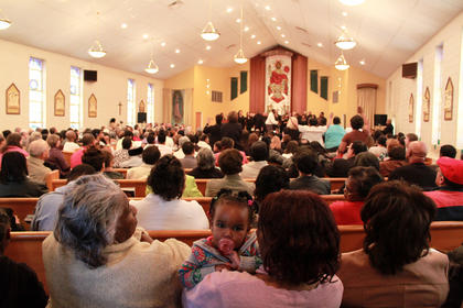 Missy Downs holds granddaughter Kamiya Downs, 16 months, as great-grandmother Frances Downs looks on at the Martin Luther King Day celebration at St. Monica Catholic Church in Bardstown Monday.