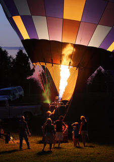 Folks gather around a balloon to see just how it works at Tuesday's Balloon Glow event at the Nelson County Fairgrounds.