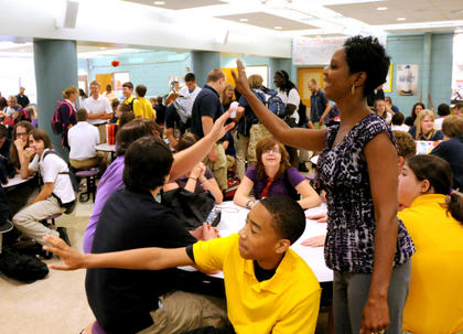Special education teacher Lucretia Young gives a student a high five in the cafeteria at Bardstown High School on the first day back Wednesday.