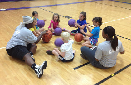 A group of kindergartners work with Bardstown High School players on dribbling and ballhandling at the recent Bardstown Lady Tigers basketball camp.