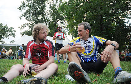Adam Jonas, Lexington, and Larry Wheeler, Lexington, rest on the lawn at Spalding Hall after completing the 100-mile route Saturday.