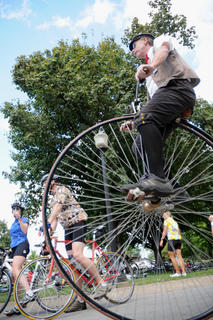 Carson Torpey, co-captain of the Kentucky Wheelmen, pedals a high wheel bicycle, known as a penny farther on Xavier Drive near Spalding Hall Saturday. The 34th annual Old Kentucky Home bike tour rolled through Bardstown Saturday and Sunday.