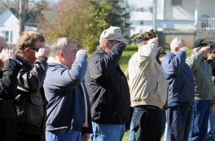 Vietnam War Veterans from the Bloomfield area stand at attention and salute while taps are played at Bloomfield Memorial Park on Veteran's Day.