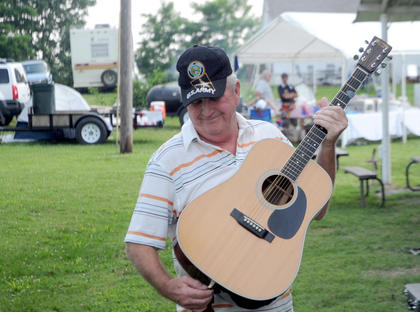 Robert Cornett secures a strap to his acoustic guitar at The Bardstown Bluegrass Festival, moments before taking the stage Saturday. Cornett plays for Wolf Creek Grass, from Southeastern Kentucky.