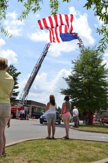 Two ladder trucks from visiting fire departments extended their boom to hang a massive flag, forming an arch for the Jason Ellis funeral procession to pass through.