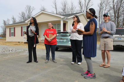 Lucretia Starnes, left, president of My New Kentucky Home Habitat for Humanity, speaks Sunday at the dedication ceremony for Nelson County's newest Habitat homeowners, Sharon Bolin, second from left, and Kimberly Phillips, second from right. Also pictured are Sydina Bradshaw, former vice president of  the affiliate, and her successor, Muncie McNamara.