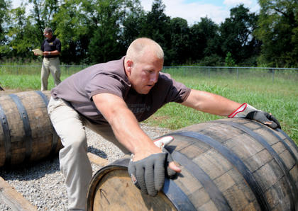 Greg Mattingly rolls a barrel at Heaven Hill Distillery Monday. Mattingly and his teammates were practicing for the Barrel-rolling Competition at the Kentucky Bourbon Festival.