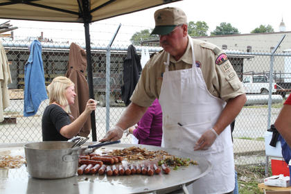 Danny Suratt cooks for the Boy Scout Troop 136 booth Saturday.