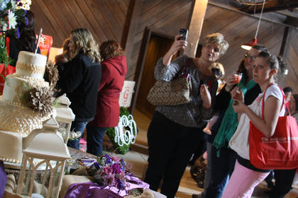 A group of attendees at the Kentucky Standard Bridal Show admire a cake on display.