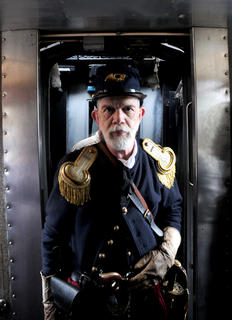 """James """"TR"""" Jones stands at attention on a passenger car."""
