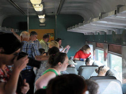 Guests on a passenger car watch as Confederate and Union reenactors fight in a staged battle near New Haven.