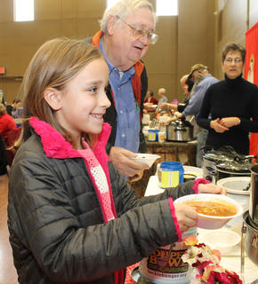 Caroline Mattingly smiles after receiving a bowl of vegetable beef soup at the Souper Bowl of Caring Saturday at St. Joseph Hall.