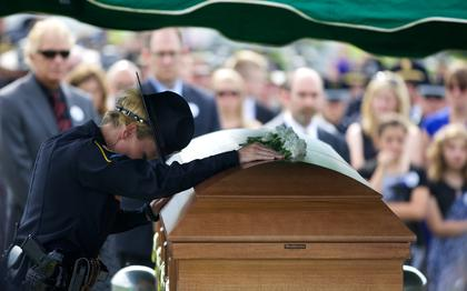 A Bardstown Police officer pays her last respects to Jason Ellis.