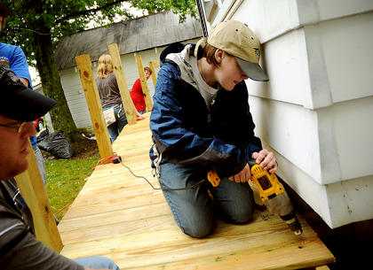 Emily Towles uses a power drill on a construction project in Bloomfield Wednesday.