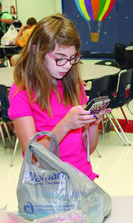 Katelyn Gioffre checks her texts during breakfast on the first day of classes at Old Kentucky Home Middle School.