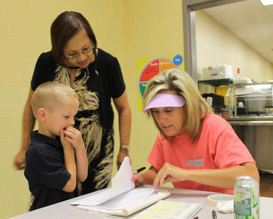 """It's my first day,"" Zachary Hillard tells lunchroom worker Denise Culver, right, while nervously chewing his fingernails. Paula Stone, left, helps look for the kindergartner's name on the list at Bardstown Primary. Thursday was back-to-school day for children in the city school system."