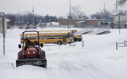 School buses sit idle on the 12th snow day this year for Nelson County Schools, while Patrick Cundiff, plows the road between Old Kentucky Home Middle School and Nelson County High School. Cundiff, a 2013 graduate of NCHS, is a maintenance employee for the school system.