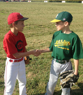 Cousins Jackson Boone and Lawson Strenecky shake hands before their playoff game against each other last week at Dean Watts park.