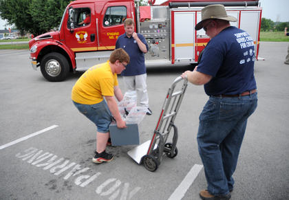 Tyler Scrogham, 13, lifts a container full of money collected by Nelson County Emergency Management Agency. His father, Terry Scrogham, hauls the money to a Brinks Armored car nearby.