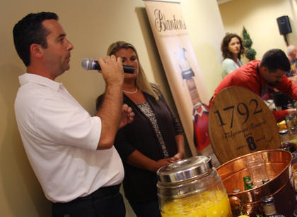 """Josh Hollifield, who represented Barton 1792 Distillery at Wednesday's Mixed Drink Challenge, fields questions about his mixed drink, """"Rosemary's Ride,"""" which won first place in the distillery division."""