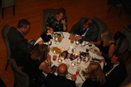 A table discusses a possible answer to a question during the trivia night portion.