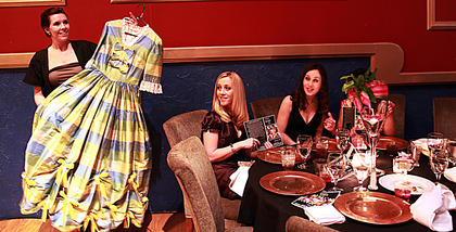 """Eulanda Clark, Bardstown, right, and Rhonée Rodgers look on as Jennifer Warren holds up a dress worn in productions of """"The Stephen Foster Story."""" Donations for up to five new costumes in the production were collected at the Feb. 12 Beautiful Dreamer's Ball, a fundraiser for the Stephen Foster Drama Association."""