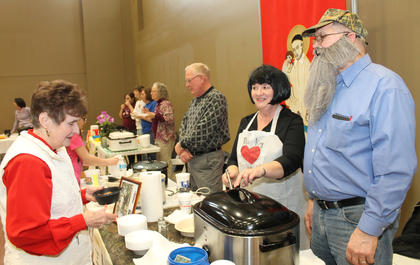 """Duck Dynasty"" stars Miss Kay and Phil Robertson (Rose and Joe Mattingly) offered a venison stew to guests at the St. Vincent de Paul Society table at the Souper Bowl of Caring benefit for the society's food bank."