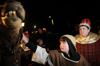 Dustin Price, who plays a shepherd in the living Nativity at Bardstown Baptist Church, handles a camel. Daniel Milby, who plays the role of a king, stands nearby.