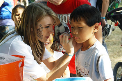 Kelly Feldman, a senior at Bethlehem High School, paints a spiderweb on 6-year-old Gus O'Daniel's face in front of Bardstown City Hall for the annual Rotary Club Kids Day Thursday.