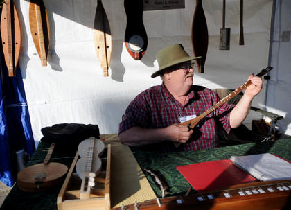 "Walter French, Boston, owner of Walt's Creations, sells his instruments at the Bardstown Arts Crafts and Antiques Fair. French plays a ""piddle-stick,"" which is a one-stringed instrument with the same scale as a dulcimer."