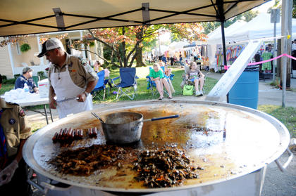 Boy Scout Troop 136 cooks hot dogs and other food on a large skillet at the Bardstown Arts, Crafts and Antiques Fair Saturday. Tom Pike stands in the background.