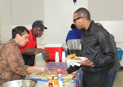 The Rev. Chris Rhodes, a priest of the Basilica of St. Joseph Proto-Cathedral in Bardstown, a former Army infantryman and a member of the Kentucky Army National Guard, is served dinner by members of the American Legion Abraham Lincoln Post 167.
