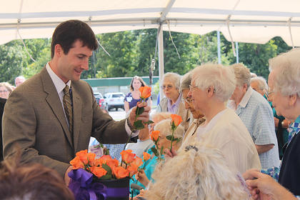 Shane Fitzgerald, mission leader for Flaget Memorial Hospital, hands out orange roses to nuns of the Sisters of Charity of Nazareth at the dedication ceremony. The nuns were recognized for their contributions to Flaget and health care in Kentucky.