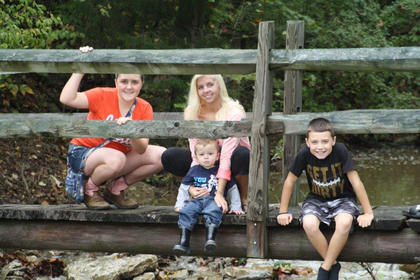 Dannielle Gilkey, Jami Rogers, Layne Bartley and Ayden Gilkey, crossing a footbridge, watch the rushing creek waters near Cox's Creek. They are the  grandchildren of Jimmy and Patsy McGee.